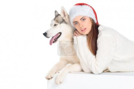 husky dog and lovely girl in santa hat, isolated on white