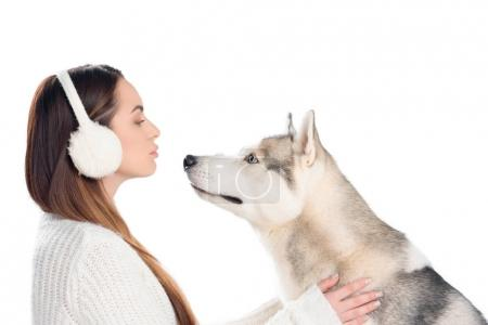 husky dog and beautiful woman in winter earmuffs, isolated on white