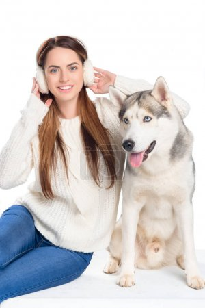 husky dog and beautiful smiling woman in winter earmuffs, isolated on white