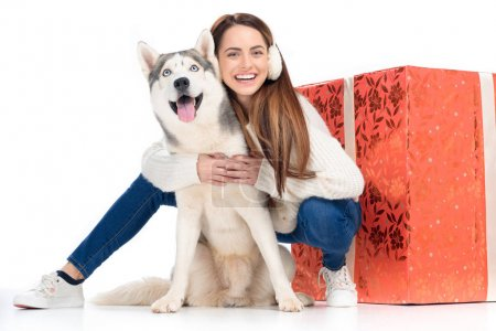 husky dog and laughing woman in winter earmuffs with big christmas gift behind, isolated on white