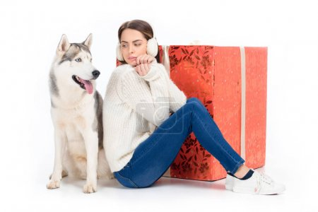 husky dog and attractive woman in winter earmuffs with big christmas gift behind, isolated on white