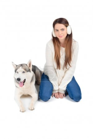 siberian husky dog and attractive woman in winter earmuffs, isolated on white