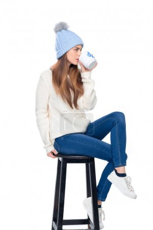 beautiful woman in knitted hat drinking coffee while sitting on stool, isolated on white