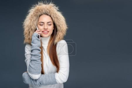 smiling woman in fur hat talking smartphone, isolated on grey