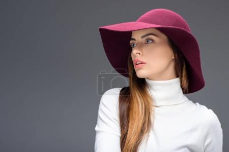 Photo for Attractive woman posing in burgundy felt hat, isolated on grey - Royalty Free Image