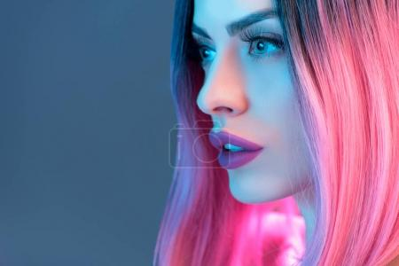 portrait of beautiful woman in pink wig, isolated on blue