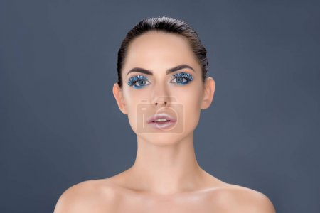 portrait of beautiful naked woman with winter makeup with glitter, isolated on grey