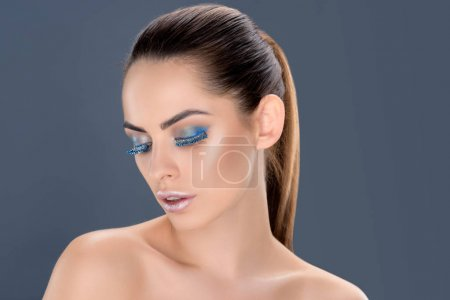 portrait of beautiful sensual woman with closed eyes with winter makeup and glitter, isolated on grey