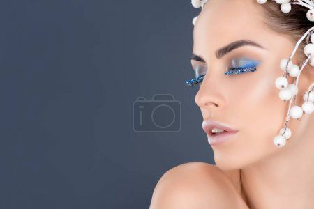 beautiful woman with closed eyes with winter makeup and glitter, isolated on grey