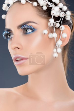 attractive model with hair accessory, winter makeup and glitter, isolated on grey