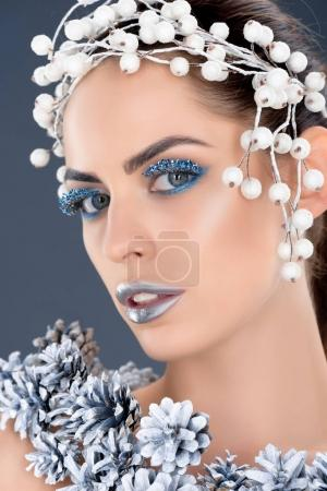 attractive model with hair accessory, christmas pine cones, winter makeup and glitter, isolated on grey