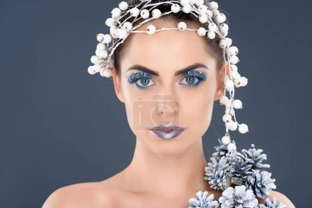 portrait of beautiful woman with hair accessory, christmas pine cones, winter makeup and glitter, isolated on grey