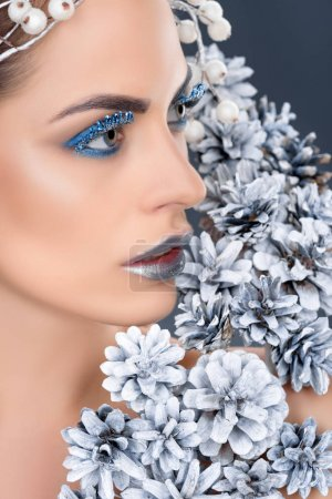 beautiful woman with christmas pine cones, winter makeup and glitter, isolated on grey