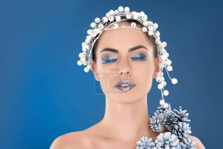 portrait of beautiful woman with hair accessory, christmas pine cones, winter makeup and glitter, isolated on blue