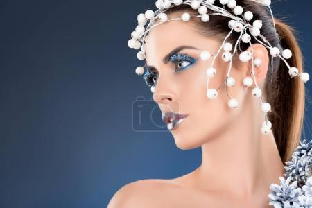 attractive model with hair accessory, christmas pine cones, winter makeup and glitter, isolated on blue