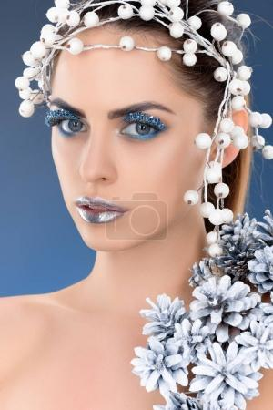 portrait of beautiful charming woman with hair accessory, christmas pine cones, winter makeup and glitter, isolated on blue