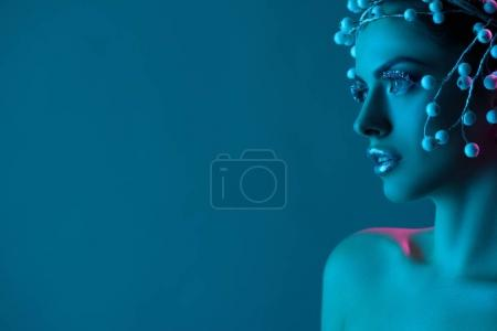 beautiful woman with hair accessory, winter makeup and glitter posing for fashion shoot, isolated on blue