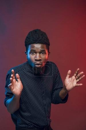 surprised african american man looking at camera isolated on burgundy