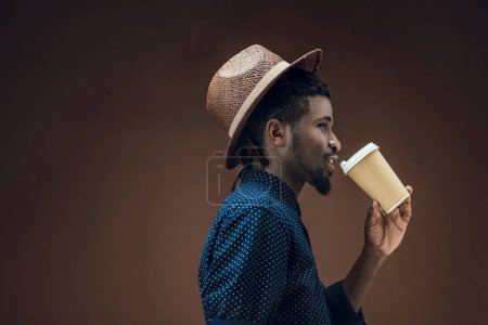 side view of african american man drinking coffee isolated on brown