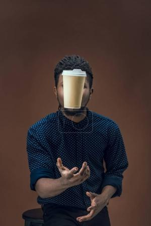 african american man catching disposable coffee cup isolated on brown