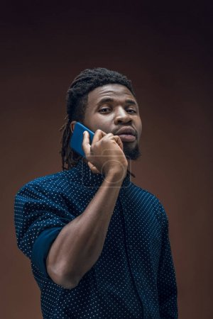african american man talking by smartphone isolated on brown