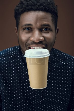african american man holding disposable coffee cup with teeth isolated on brown
