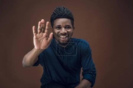 Photo pour Souriant homme afro-américain donnant haute cinq isolé sur brun - image libre de droit