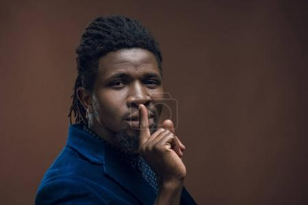 Photo pour Homme afro-américain montrant geste de silence isolé sur brun - image libre de droit