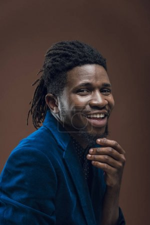 Photo for Smiling african american man touching beard isolated on brown - Royalty Free Image