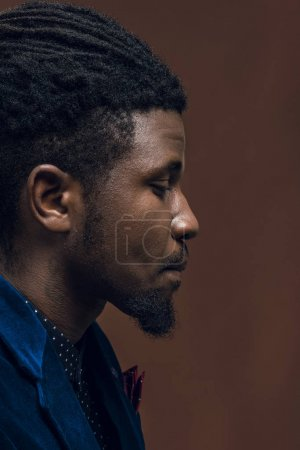 side view of handsome african american man with dreadlocks isolated on brown