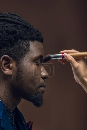 cropped image of woman applying foundation powder with makeup brush on african american man face isolated on brown