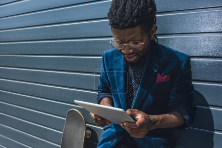 Stylish african american man in blue jacket looking at tablet