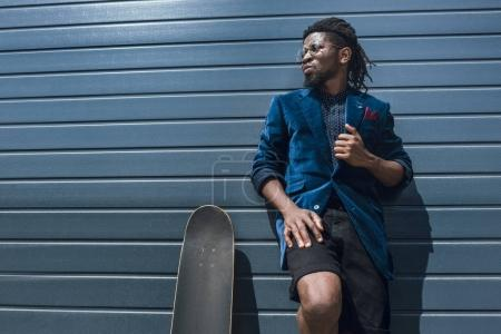 stylish african american man in blue jacket leaning on striped wall and looking away