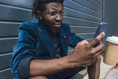 stylish african american man in blue jacket holding coffee to go and using smartphone