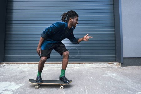 stylish african american man in blue jacket skating on street and pointing on something