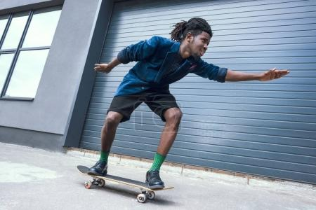 stylish african american man in blue jacket skating on street