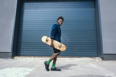 stylish african american man in blue jacket with skateboard walking on street