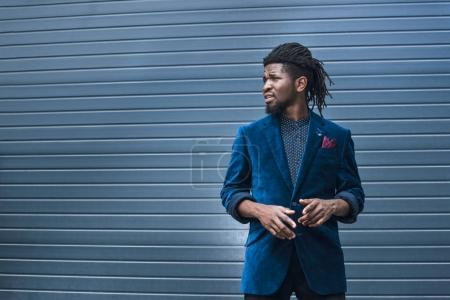 stylish african american man in blue jacket looking away