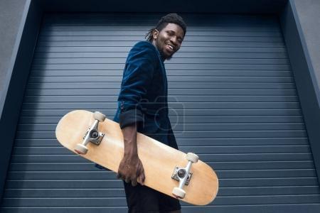 Photo pour Vue du dessous de l'élégant homme afro-américain dans une veste bleue avec planche à roulettes - image libre de droit
