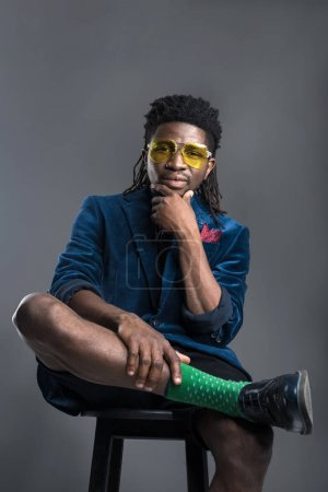 stylish african american man in blue jacket and yellow sunglasses isolated on gray