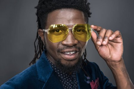 handsome african american man in yellow sunglasses looking at camera isolated on gray