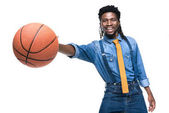smiling african american man playing with basketball ball isolated on white