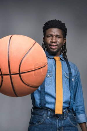 african american man playing with basketball ball isolated on gray