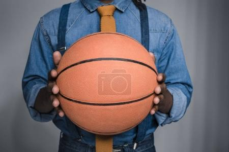 cropped image of african american man holding basketball ball isolated on gray