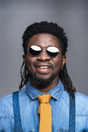 Foto de Sonriente hombre afroamericano en negro gafas de sol aislados en gris - Imagen libre de derechos