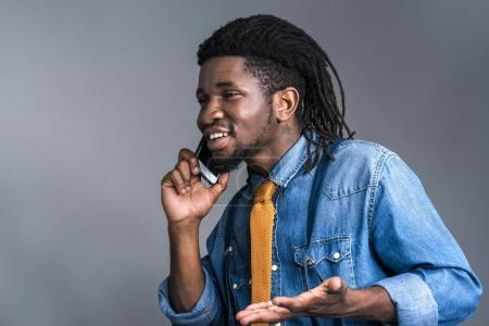 happy african american man talking by smartphone isolated on gray