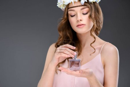 attractive young woman in floral wreath smelling perfume isolated on grey
