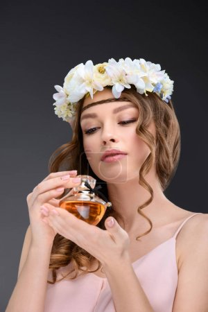 beautiful young woman in floral wreath smelling perfume isolated on grey