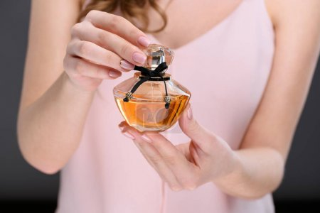 cropped shot of woman opening bottle of perfume