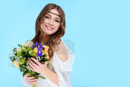 happy young woman holding floral bouquet isolated on blue